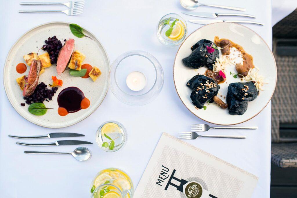 Nakryty stół restauracyjny. Na talerzach kolorowe dania