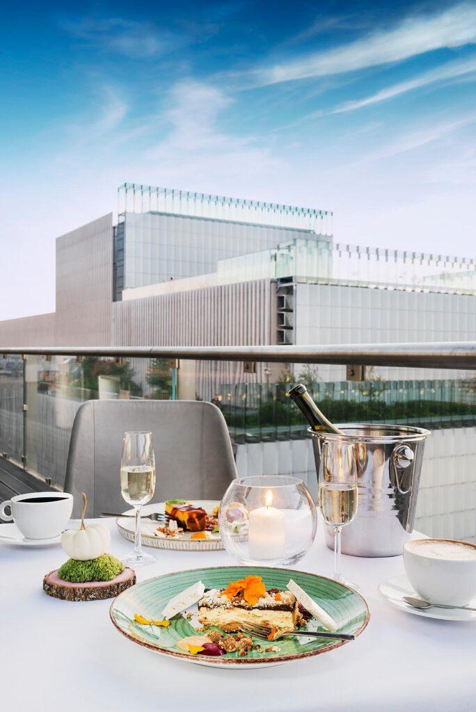 Widok na Centrum Spotkania Kultur z tarasu restauracji 2 PI ER. Na pierwszym planie nakryty stół z posiłkami