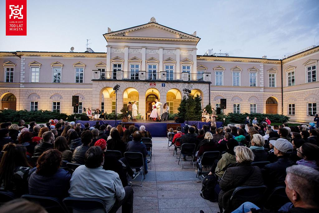 Pokaz Legenda o Czarciej łapie na placu Litewskim Na pierwszym planie siedzi widownia, a w głębi na scenie tańczą tancerze.Czarciej łapie na placu Litewskim