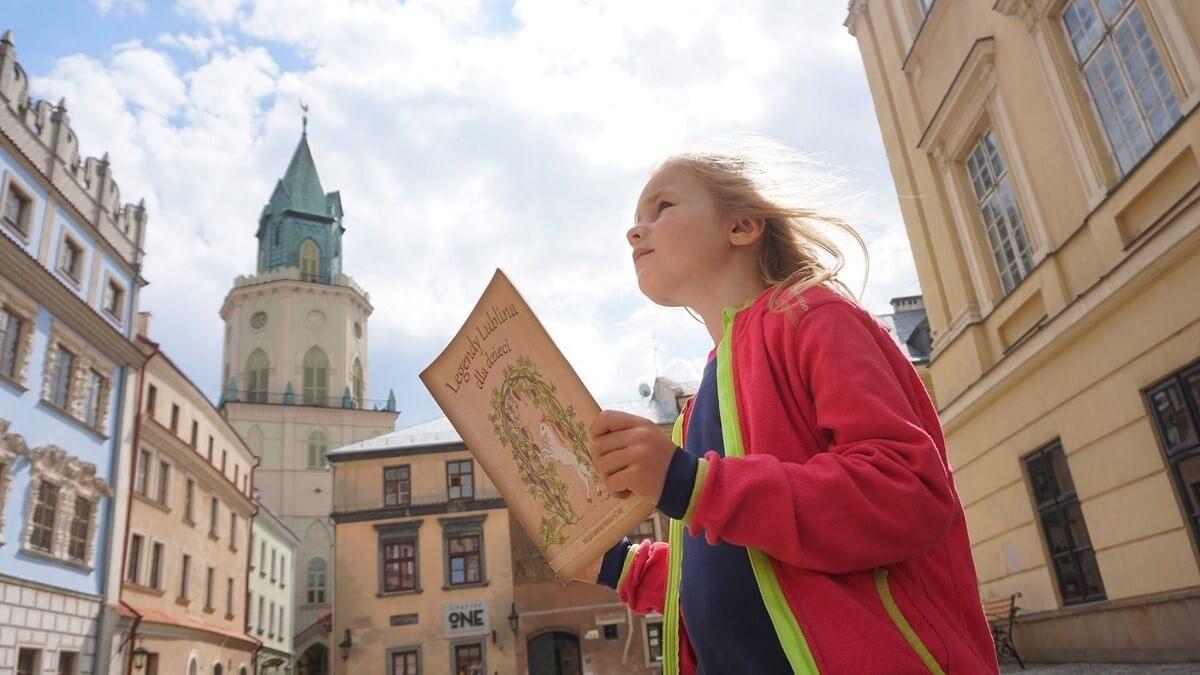 Dziewczyna z ksiażką o lubelskich legendach na tle Wieży Trynitarskiej