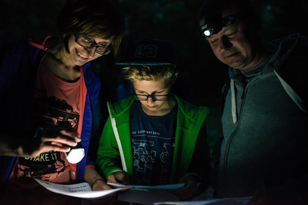 Troje młodych osób z latarką patrzy na kartkę papieru