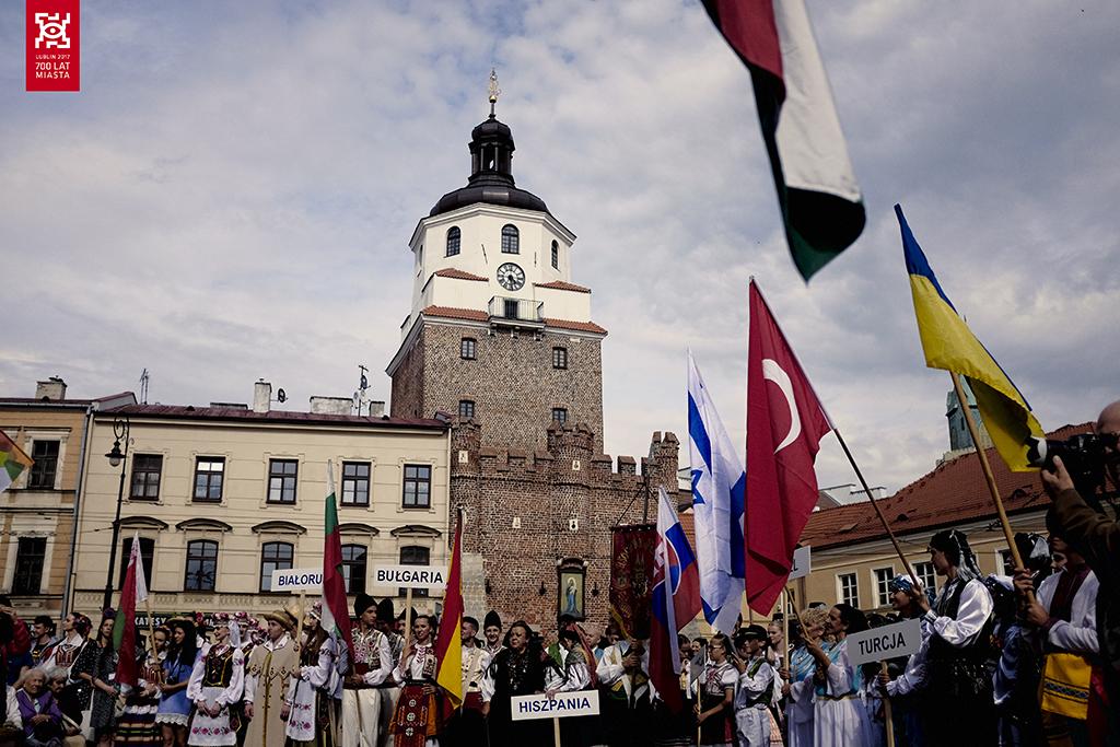 Międzynarodwe Spotkania Folklorystyczne - ludzie z flagami różnych państw na Placu Łokietka