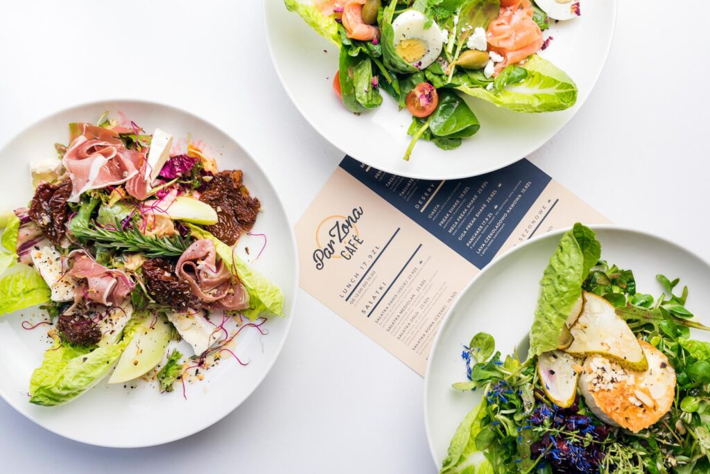 Talerze z daniami na stole, karta menu w Par Zona Cafe