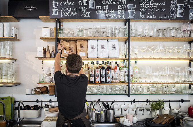 Półki z herbatami, kawami i szkłem w kawiarni Parzona