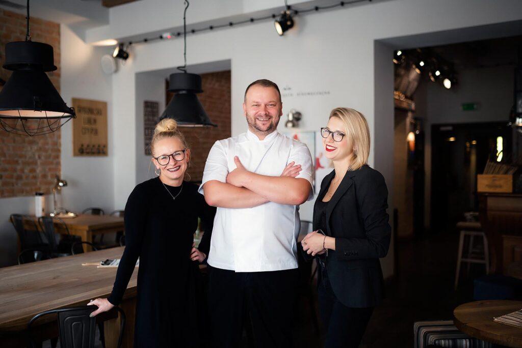 Szef kuchni Trybunalska City Pub w towarzystwie dwóch kobiet z personelu