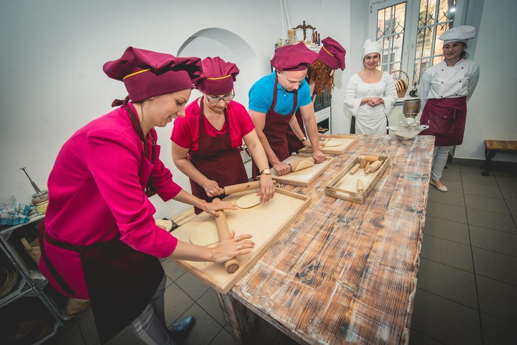 Trzy kobiety wałkują ciasto podczas warsztatów wypieku cebularza