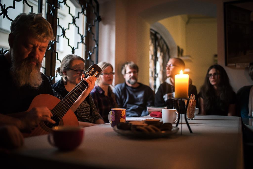 Grupa ludzi przy stole śpiewa piosenki przy akompaniamencie gitary