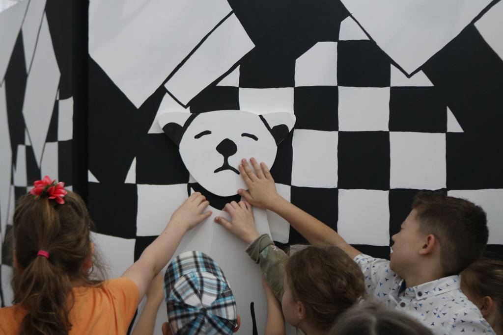 Czworo dzieci podziwia dzieło w formie psa