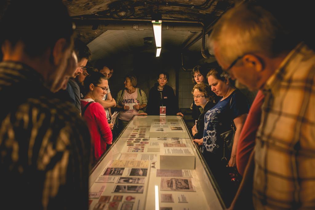 Grupa osób zwiedza wystawę w podziemiach Browaru Perła