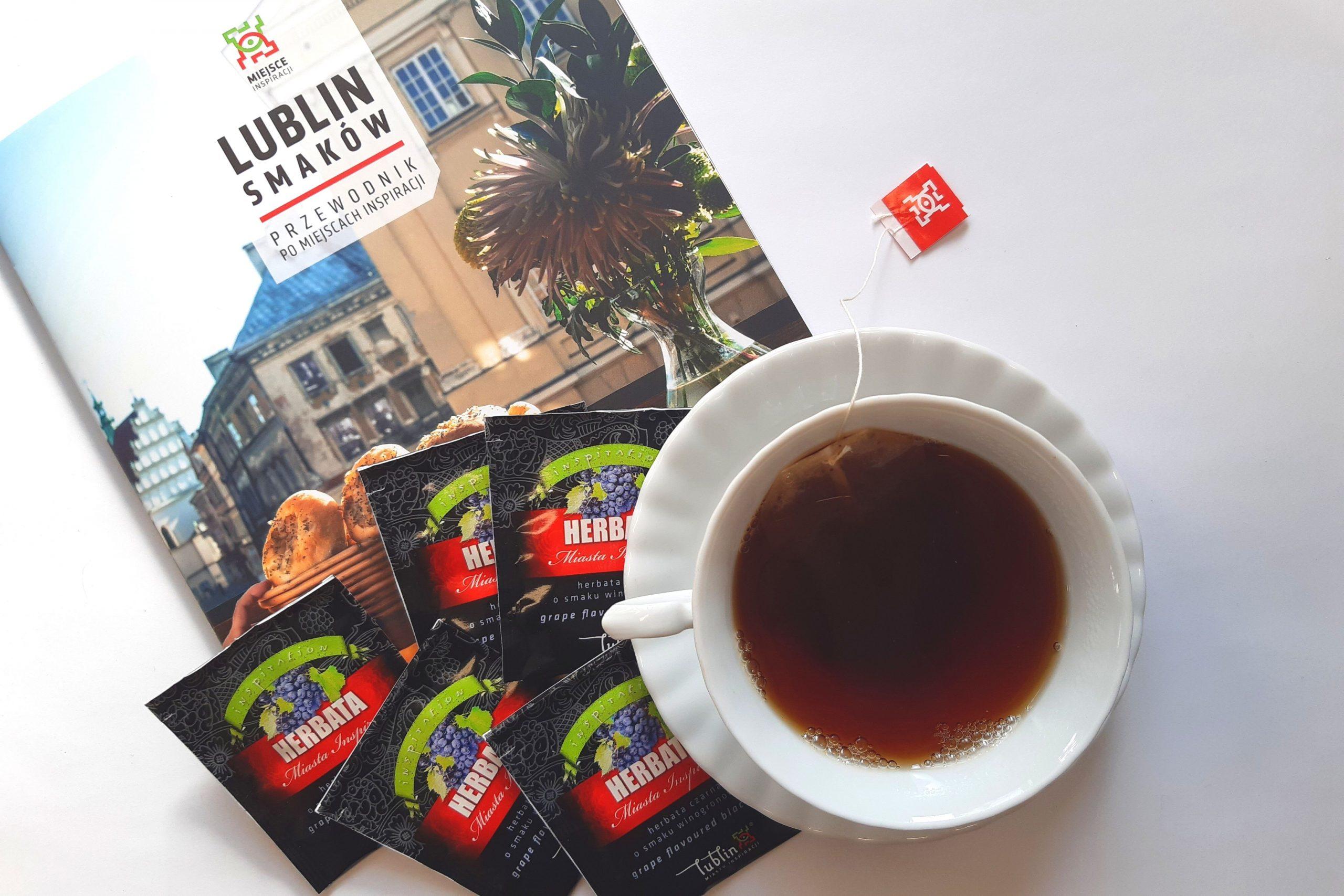 """Filiżanka herbaty, obok torebki herbaty i folder """"Lublin Smaków""""."""