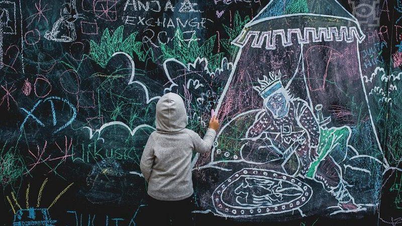 Dziecko przy tablicy maluje kredą